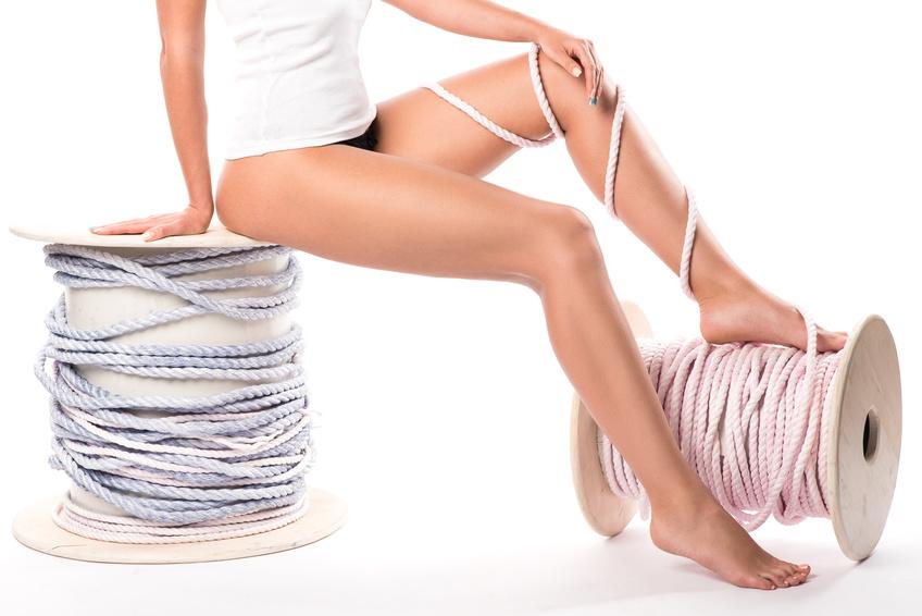 Slender woman's legs tied with rough rope. Elegant slender female legs, two rope bobbins.